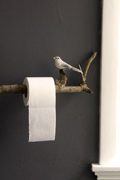 Easy diy for toilet paper! With a tree branch and a bird. I would use to hang other things , but the idea is very nice for both the home and the garden
