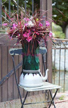 Roxane Maffre a choisi cette bouilloire pour fusionner les dahlias noirs, clématites, hortensias roses, baies de roses, raisins d'Amérique, panicums bordeaux et feuilles de magnolia. Création extraite du Carnet d'Idées #Interflora ! #artfloral #fleurs