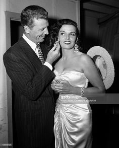 Actor Dan Dailey examines actress Jane Russell's earrings at an event in 1953.