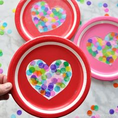 This heart suncatcher craft is simple, colorful and perfect for an afternoon Valentine's Day craft. All you need is paper plates, color confetti and clear contact paper to make this colorful heart suncatcher craft for Valentine's Day.