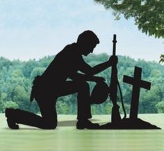 Silhouette of kneeling soldier against photo background. Very moving.