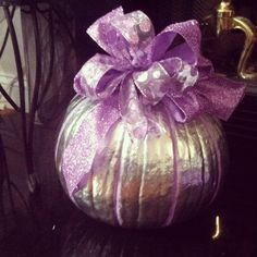 This was easier than carving. I took metallic silver spray paint and sprayed the whole pumpkin. I took regular wall paint (it was satin finish I think, something with a little shine) I took a small paintbrush and filled in lines, spaced accordingly. I then took the silver spray paint again and spritzed it to give the purple paint a little extra shimmer. I took two different purple wire ribbons (left over from my Christmas wrapping) and made 2 bows, combined them to make 1 big bow. Simple.