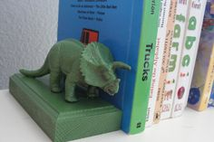 DIY bookends: take a two bevelled pieces of wood, spray paint them and two similarly scaled toys and hot glue together.