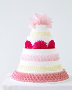 Paper ornaments in bright shades are a style-savvy and budget-friendly way to decorate an all-white cake