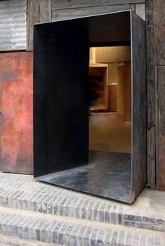 Stunning metal entrance design transforms the humble building materials surrounding and draws you into the space. Beautiful mix of textures and weathered finishes.