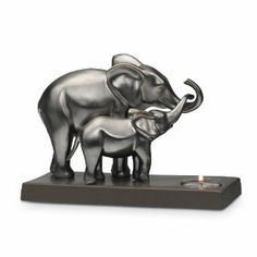 A heartwarming moment between mother and baby is captured in glazed ceramic. The gray metallic finish reflects the shimmering glow of a tealight, sold separately. 6 1/4h, 9w.
