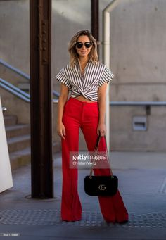 A guest wearing red wide leg pants, striped top, Gucci bag at day 4 during Mercedes-Benz Fashion Week Resort 18 Collections at Carriageworks on May 17, 2017 in Sydney, Australia.