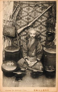 """Ainu man with his tools and weapon from """"The Customs of Hokkaido tribe"""" series, ca. 1910"""