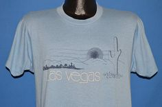 Chest 19 in.  Length 26 in.   Content: 50/50 Poly/Cotton  Tag Brand: Screen Stars  This blue vintage t-shirt has a graphic of the city of Las Vegas skyline. The image shows the desert hills surrounding the city in addition to a cactus and a sunset.  The tag on the shirt says Large, but it fits like an Adult Medium.         17-06-75574
