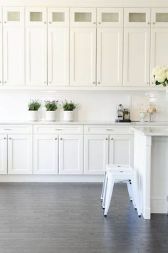 Classic recessed panel kitchen cabinets in crisp white with gray flooring.