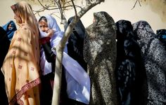 Afghan women turn out to vote in the first democratic transfer of power the country has ever seen. [2014]