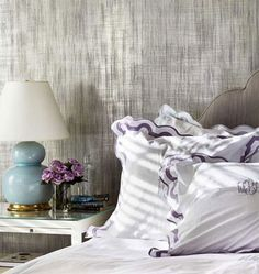 linen and lavender.  love the textured grey walls, gourd lamp, and scalloped headboard.