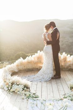 White pampas grass surrounding the couple lends such a dreamy feel to their wedding ceremony!
