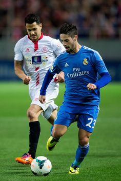 Isco competes for the ball with Vitolo during the La Liga match between Sevilla FC and Real Madrid CF at Estadio Ramón Sánchez Pizjuán on March 26, 2014 in Seville, Spain.