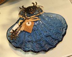 Blue glass shell held by metal crab. Included are starfish tongs so this darling dish can be whatever you want it to be!  Also makes a cute soap dish.