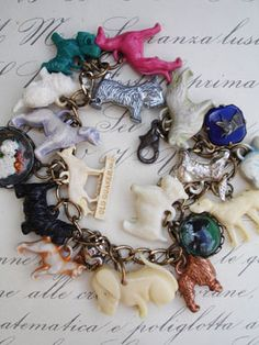 Vintage Dogs Charm Bracelet with Purple Hound   This one has 18 different, vintage, dog charms including celluloid, metal, glass cabochons. All the charms are vintage and special and many breeds are represented including: Scottish Terriers, Poodles, German Shepherd, Collies, mutts and more! One is a purplish hound! ...