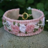 Lovely pale pink and white roses, in a cloud of white gypsophila, have been embroidered onto a pale pink, felt background. The bracelet is edged in blanket stitch, in pink, lined with ivory and closes with a toggle clasp. The toggle fastening is loosel...
