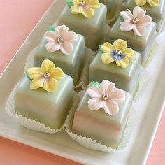 Fondant Flower Toppers | baking911.com-These would be pretty with white icing and blue icing squares and then reversed color flowers on the top.