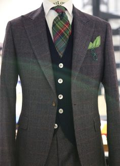 A Peak lapel, one button single breasted, and different types of plaid fabric matching with a blue cardigan