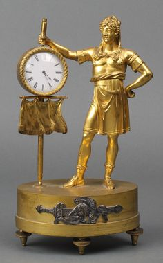 "Lot 870, A Regency Continental table timepiece in the form of a standing centurion with banner, having an enamelled dial with Roman numerals contained in a gilt ormolu case 9 1/2"" est £160-200"