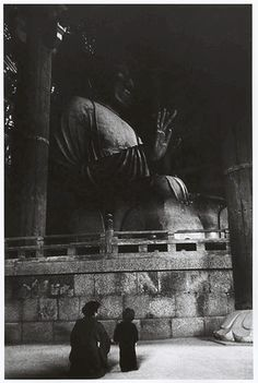 Robert Capa, [Adult and child sit beside a giant Buddhist statue, Nara, Japan], April 1954