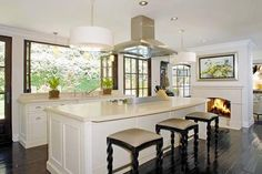 I like the kitchen with all the windows, the fireplace, and the dark walnut floors: