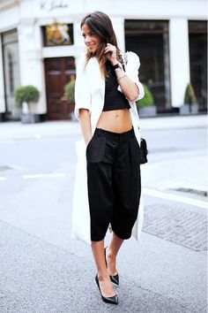 A black crop top is worn with culottes, a white duster, shoulder bag, and black pumps