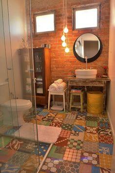 Esse banheiro projetado pela designer de interiores Ana Paula Magalhães tem piso formado por um patchwork de ladrilhos hidráulicos criados pelo artesão Sérgio Viecili. O elemento confere um ar rústico ao ambiente, onde se destaca também a parede de tijolinhos