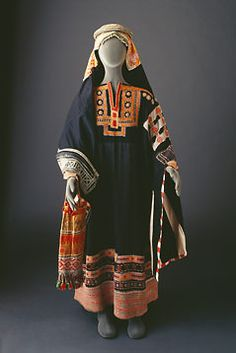 Sulaym thobe with finely embroidered yoke. The sleeves have patchwork along the shoulders and around the edges. The circular iqal (head-band ) is made of woven leather interspersed with silver beads and bound around a malleable core.