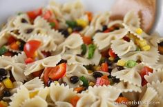 Southwest pasta salad with peppers, black beans, corn, green onions, tomatoes and cheese with a cilantro lime vinagrette