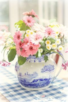 Love the blue and white pitcher with a brighter color flowers in reds, orange, boxwood and greens, etc