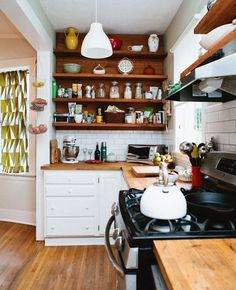 integated wooden countertops, tile backsplash, open shelves, and brick wall. perfect!