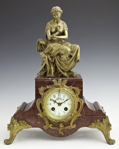 Bronze over Copper and Marble Mantel Clock, 19th c., by A. D. Mougin, the top with a seated Cleopatra in classical dress, over a clock with an enamel dial with painted floral decoration, on a shaped base on scrolled feet.