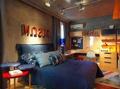O quarto do adolescente com tema na música e usando o jeans como inspiração cromática. Nas paredes, o revestimento sustentável com aspecto de concreto dá uma aparência despojada ao projeto. A iluminação indireta deixa o ambiente moderno ainda mais aconchegante