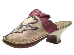 Pair of woman's mules, France, 1774-1792. White ribbed silk, trimmed with dark pink silk ribbon, silver metal thread embroidery.