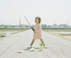 Lo sfondo è sempre uguale, ma le fotografie di questa bambina sorprendono ogni volta. Foto di Nagano Toyokazu.  #photography #kids