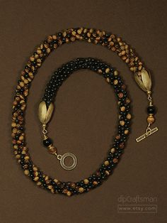FREE SHIPPING within the USA!  Tiger Eye and Onyx Necklace.  An iridescent gemstone, Tiger Eye is believed to bring focus and confidence to its wearer. Black Onyx quickly enhances the retention of memory and promotes attention to detail.  Rich brown tiger eye paired with polished black onyx in a gradated pattern. The gradation in the necklace was created by braiding them together in the Kumihimo style. The braids gradate from black onyx on one side to a rich, medium Brown Tiger Eye on the…