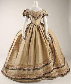 Silk evening dress, British, ca 1860-64. Low body, deep front point; double short sleeve; bertha; box pleats and directional pleats in skirt. Trim is box pleated ruched ribbon between a blonde lace and a black lace; singular on bertha and sleeves, doubled on skirt. MET