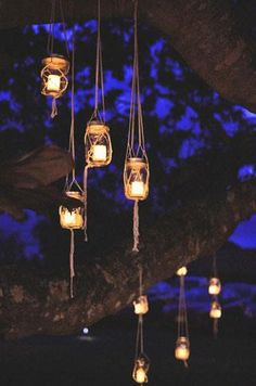 Candle-filled mason jars in jute hangers, suspended from tree branches.