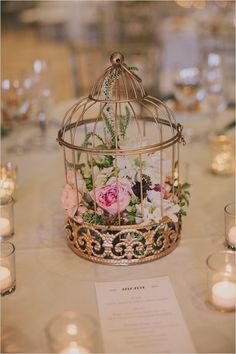 I love this centerpiece! The golden cage is great, but the combination with the flowers is even better. ~A