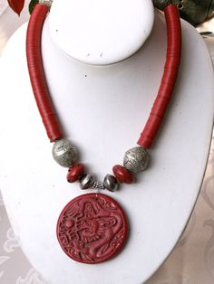 by Anne Marie | A red bakelite pendant from the Revival Period (1930/40s) with Chinese ornaments and dragon is strung on a necklace of silver over lac beads and Sherpa coral glass beads from Tibet. the matching red bakelite heishi disks come from the African Trade. The heishi have exactly the same color as the pendant.  |  BeadArt Austria Designs | SOLD