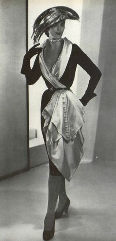 1950 Model in black satin dress featuring a low-cut white satin shawl collar that descends into a buttoned side panel by Jacques Fath