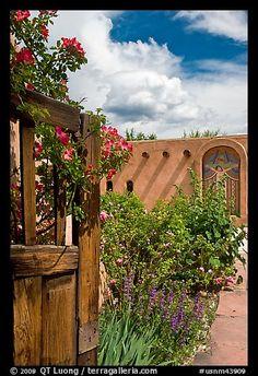 Gardens and adobe wall, Sanctuario de Chimayo. New Mexico, USA