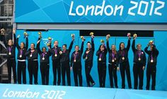 The U.S. women's water polo team show off their gold medals on the podium.