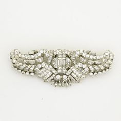 """ART DECO PLATINUM DIAMOND DOUBLE-CLIP BROOCH  Brooch designed as stylized winged Horus, detaches to form mirror pair of dress clips, ca. 1930. Half-moon, baguette, marquise and circular cut diamonds, approx. 6.10 cts. TW. Unmarked. 14.1 dwt. (22 gs.), 2 3/4"""" x 1"""""""