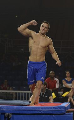 A dark-haired young man wearing blue shorts raises his fist in the air while standing on a mat. - Imgur