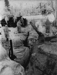 Soviet tanks and infantry move through the snow.