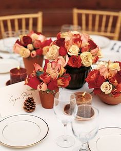 Small terra-cotta and copper pots filled with roses, tiny pinecones, and vanilla-scented pillar candles add a warm touch to reception tables.