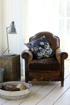 Beautiful corner of a living room interior. Old worn leather armchair with a acc. Beautiful corner of a living room interior. Old worn leather armchair with a accent pillow, wooden log side table, baske. Decor, Furniture, Home Decor Inspiration, Chair, Home Decor, Leather Armchair, Leather Chair, Armchair, Home And Living
