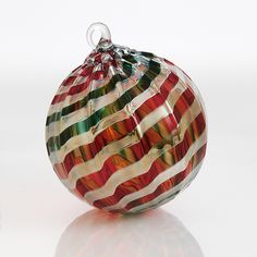 Joyeux Noel Art Glass Ornament Created by Glass Eye Studio Festive bands of red, green, and gold wrap this blown glass ornament in a whorl of holiday cheer. Artist-made in the USA.  Since this ornament is sold out, please click on the following link to view available ornaments. 'View All Ornaments'. Dimensions: 3.0in diameter Sorry, this item is currently sold out